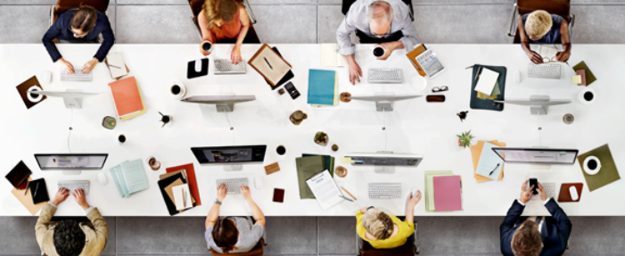 Aerial shot of eight people sitting and working at a long conference table.