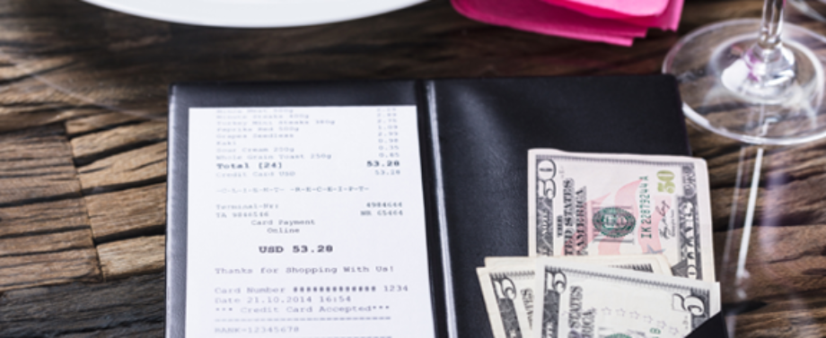 Close up of restaurant bill with tip money on table with plate, napkin and glass.