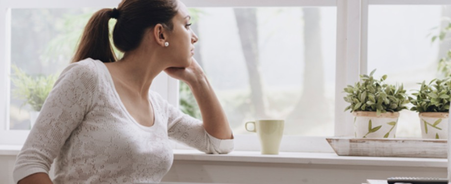 Young woman connecting with her laptop at home, she is pensive and looking out of the window.