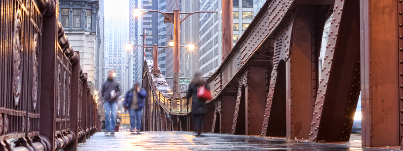 People walking across a Chicago bridge.