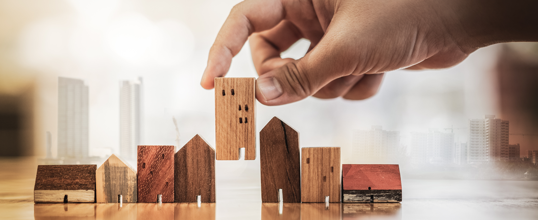Hand choosing mini wood house model from mode wood table.