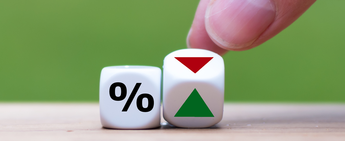 Finger touching a pair of dice with a percentage sign and a red arrow pointing down with a green arrow pointing up.