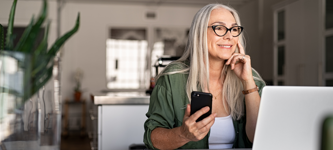 Senior woman using laptop and smartphone stock photo.